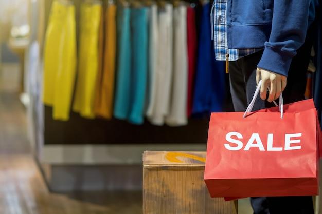販売紙の買い物袋を保持しているカジュアルな服を着た男性のマネキンの一部