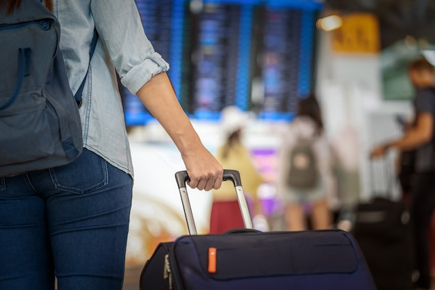 フライト情報でのチェックインのためにフライトボード上に荷物を持っているクローズアップ手