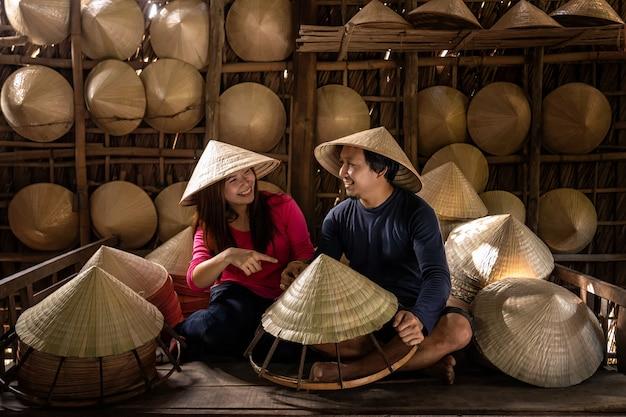 アジアのカップル旅行者職人、古い伝統的な家で伝統的なベトナムの帽子を作る