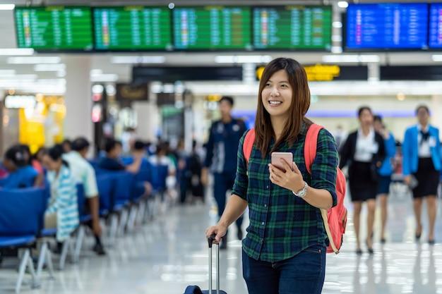 フライトボード上でチェックインのスマート携帯電話を保持している荷物を持つアジアの旅行者