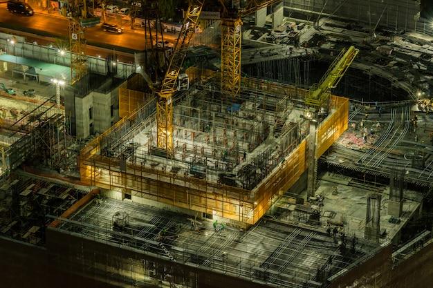 Неопределенные работники работают в строящемся здании, а краны построили здание