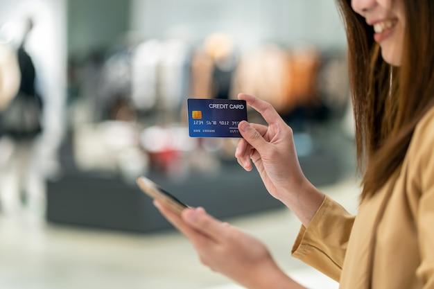 デパートでのオンラインショッピングのための携帯電話でクレジットカードを使用してクローズアップアジアの女性