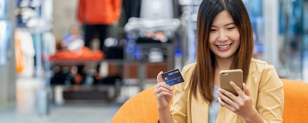 オンラインショッピングのための携帯電話でクレジットカードを使用してアジアの女性のバナー