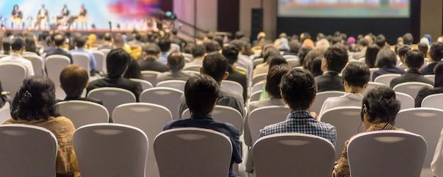 Баннер на титульном листе. вид сзади слушателей. выступающие на сцене в конференц-зале.