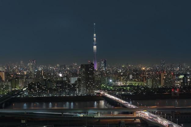 急行と川、日本のダウンタウンの街並みにまたがる東京スカイツリーのシーン