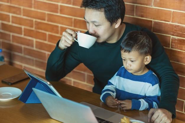 息子とアジアのシングルパパは、技術のラップトップを介して漫画を探しているとコーヒーを飲みます