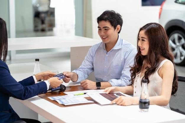 決定が新しい車を買うときにカップルの顧客からクレジットカードを受け取るアジアの店員