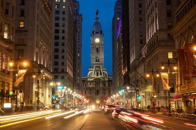 車の信号で夕暮れ時にフィラデルフィアの歴史的な歴史的な市庁舎の建物のシーン