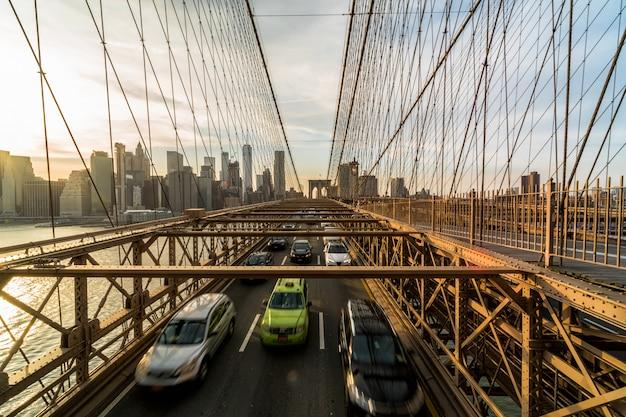 ニューヨークの街並みの背景の上のブルックリン橋の上の営業日後のラッシュアワーのトラフィック