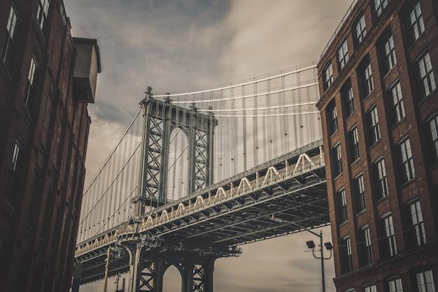 アメリカ、ニューヨークの古いれんが造りの建物とマンハッタン橋が見えるダンボー視点