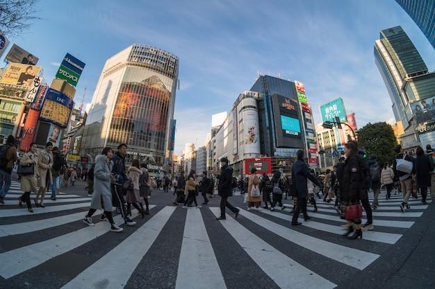 未定義の人々と車の群衆の魚眼レンズシーンは、歩行者専用交差点を歩いています。