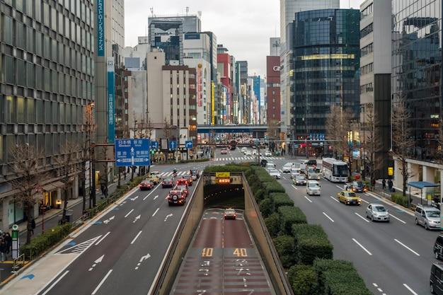多くの車と高架道路の交差点を歩いている人々のラッシュアワー交通