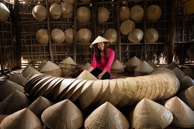 アジアの旅行者の女性職人、古い伝統的な家で伝統的なベトナムの帽子を作る