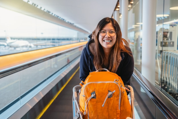 アジアの観光客が幸せで、旅行に興奮していて、エスカレーターで歩くとき、歩いて、笑って