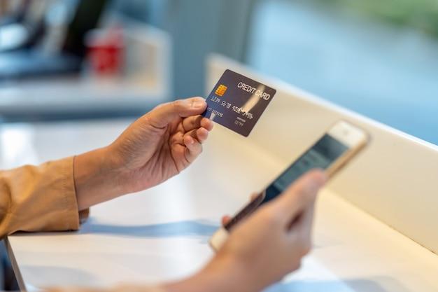 デパートでのオンラインショッピングのための携帯電話でクレジットカードを使用してアジアの女性のクローズアップ