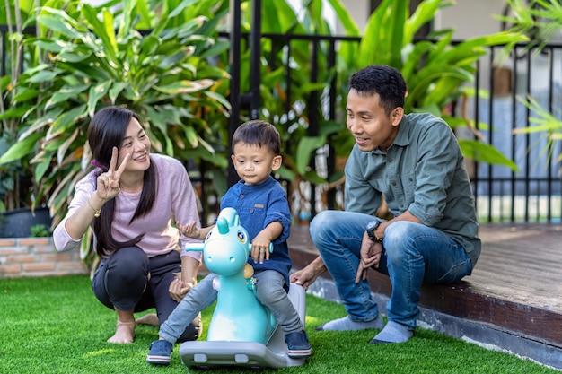 現代の家の前庭の芝生に住んでいるとき、息子とアジアの家族が一緒におもちゃで遊んでいます