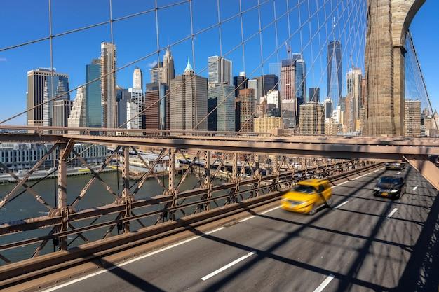 ニューヨークの街並みのブルックリン橋の上の作業日の前に朝のラッシュアワーのトラフィック