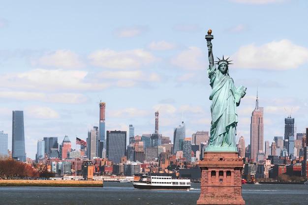 ニューヨークの街並みの川辺の風景をめぐる自由の女神像