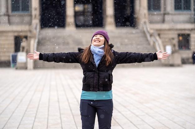 アジアの若い女性が雪が降ったときに雪を遊んで、旅行、興奮して概念
