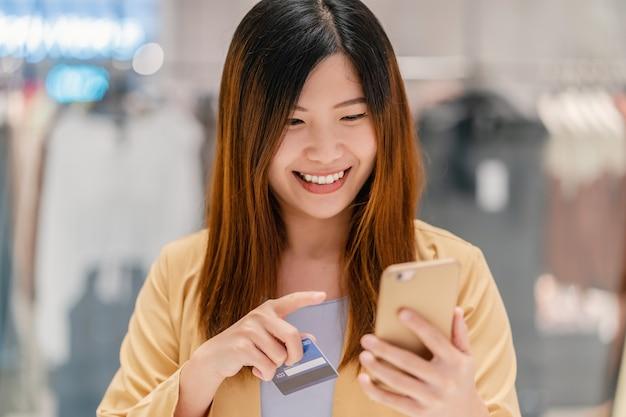 アジアの女性がデパートでのオンラインショッピングのための携帯電話でクレジットカードを使用して