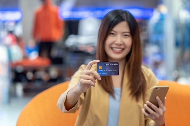 アジアの女性の肖像画を保持し、デパートでのオンラインショッピングのためのクレジットカードを提示