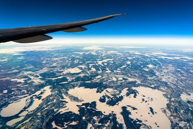 日の出、交通機関および旅行者の概念時に飛行機の側面の窓からの眺めの上の外