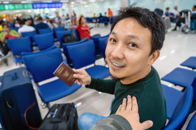 Прикосновение руки к азиатскому плечу для приветствия друга в аэропорту при ожидании полета на борту