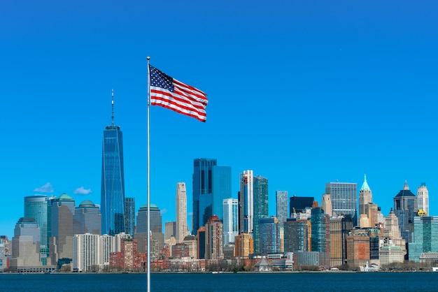 所在地がマンハッタンのニューヨークの街並み川沿いのアメリカ国旗の光景