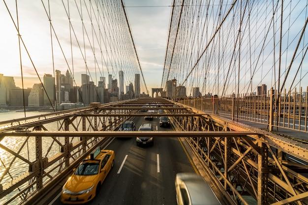 ニューヨークの街並みにかかるブルックリン橋の営業日後のラッシュアワーの交通