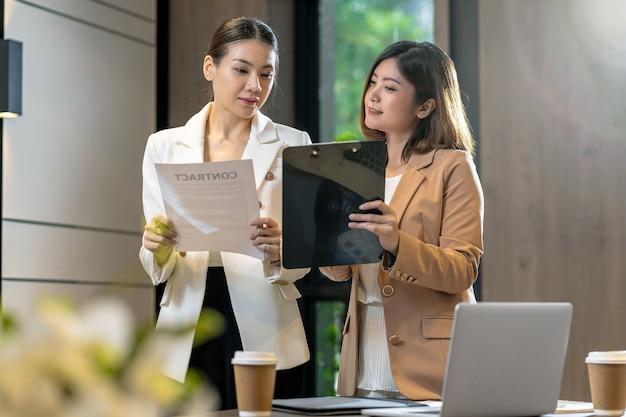 Две азиатские деловые женщины обсуждают с партнером