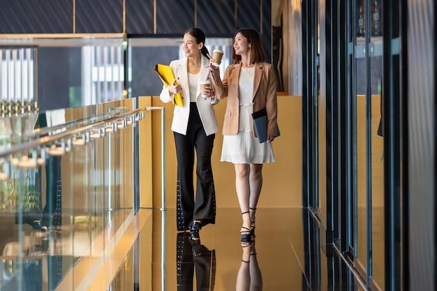 Две азиатские деловые женщины, идущие и разговаривающие во время перерыва на кофе в современном офисе или совместной работы, перерыва на кофе, расслабления и разговора после рабочего времени, партнерства бизнеса и людей