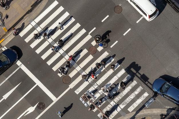 Вид сверху на пешеходов толпы неопределенных людей, идущих через улицу перекрестка перекресток с солнцем в токио, япония