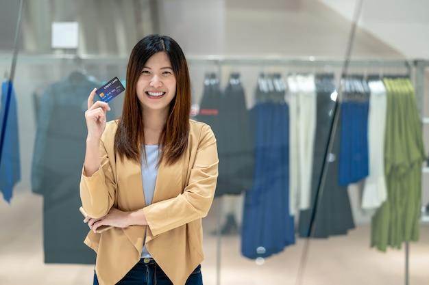 洋服店、テクノロジーマネーウォレット、オンライン決済上のデパートでのオンラインショッピングのためのスマートな携帯電話でクレジットカードを使用して肖像画アジアの女性
