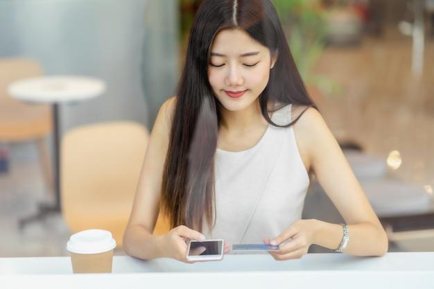 オンラインショッピングの携帯電話でクレジットカードを使用して若いアジア女性