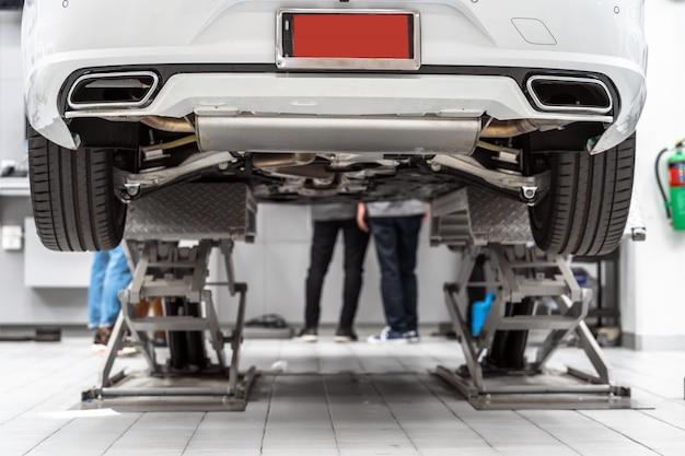 自動車サービスで持ち上げられた車の裏側とアジアのメカニックチェックとトーチタイヤ
