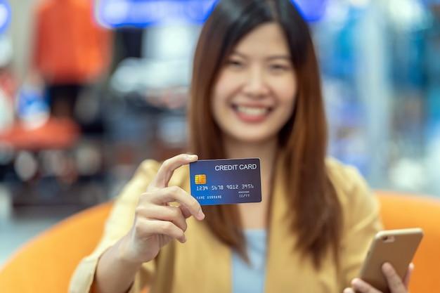 クレジットカードを保持し、オンラインショッピングのための携帯電話を提示するクローズアップアジアの女性の手
