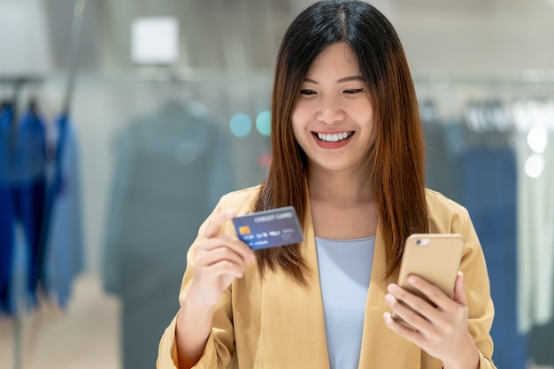 デパートでのオンラインショッピングにスマートな携帯電話でクレジットカードを使用してアジアの女性