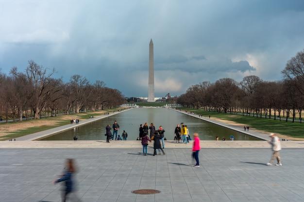 認識できないさまざまな観光客がワシントン記念塔を見ることができるアブラハムリンカーン記念館を訪れています