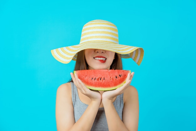 Привлекательная азиатская молодая женщина, носящая летнюю шляпу и держащая кусочек слайда арбуза на изолированной синей стене, сексуальном прикусе, копировании пространства и студии, модных путешествиях и туристической концепции