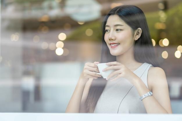 現代のコーヒーショップでコーヒーのカップを保持しているアジアの若い女性またはウィンドウミラー、日本語、中国語、韓国のライフスタイルと日常生活、起業家の概念の横にあるコワーキングスペース