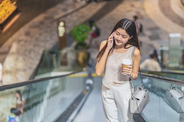 Молодой азиатский пассажир женщины используя умный мобильный телефон и идя вверх по эскалатору