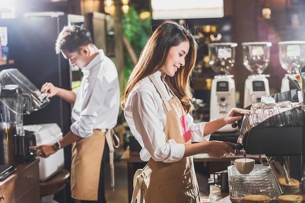 アジアのバリスタが一杯のコーヒー、エスプレッソをラテまたはカプチーノでコーヒーショップでの注文のために準備し、エスプレッソを作る