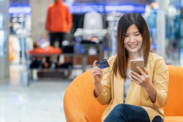 「個人認証ステップでの顔認識によるアクセス制御にテクノロジータブレットを使用しているアジアの女性
