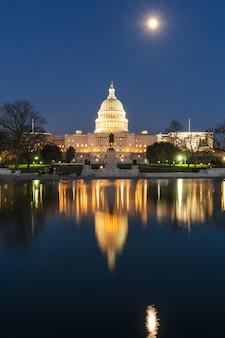 夕暮れ時の米国議会議事堂、大きなプールのある超満月の反射