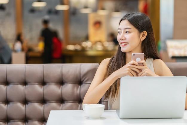Азиатская молодая женщина держа чашку кофе и используя мобильный телефон в современной кофейне