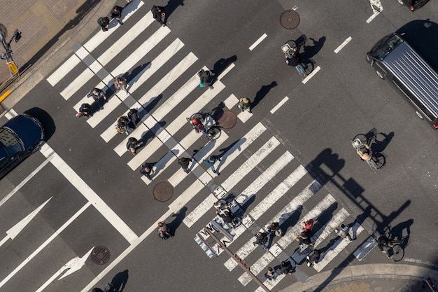 Вид сверху на пешеходов толпы неопределенных людей, идущих на эстакаде перекрестка улиц с солнечными лучами