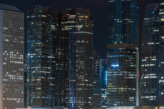 夜の時間で香港の街並みの超高層ビル