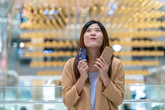 オンラインショッピングのためのクレジットカードと携帯電話を保持しているアジアの女性