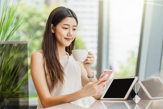 一杯のコーヒーを保持していると携帯電話を使用してアジアの若い女性