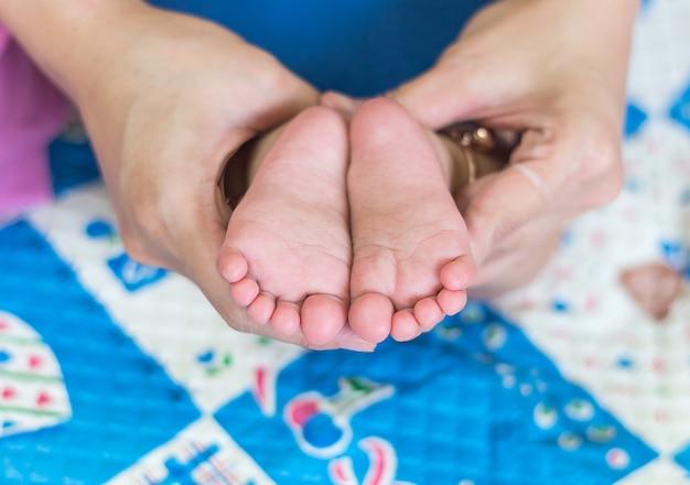 母親の手の上の赤ちゃんの足